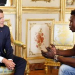 French President Emmanuel Macron (L) speaks with Mamoudou Gassama, 22, from Mali, at the presidential Elysee Palace in Paris, on May, 28, 2018.  Mamoudou Gassama living illegally in France is being honored by Macron for scaling an apartment building over the weekend to save a 4-year-old child dangling from a fifth-floor balcony. / AFP / POOL / Thibault Camus