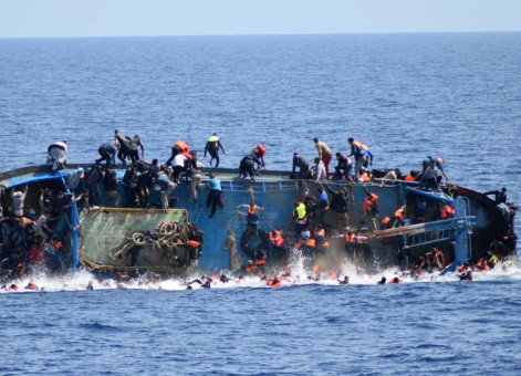 """This handout picture released on May 25, 2016 by the Italian Navy (Marina Militare) shows the shipwreck of an overcrowded boat of migrants off the Libyan coast today. At least seven migrants have drowned after the heavily overcrowded boat they were sailing on overturned, the Italian navy said. The navy said 500 people had been pulled to safety and seven bodies recovered, but rescue operations were continuing and the death toll could rise.  The navy's Bettica patrol boat spotted """"a boat in precarious conditions off the coast of Libya with numerous migrants aboard,"""" it said in a statement. / AFP PHOTO / MARINA MILITARE AND AFP PHOTO / STR / RESTRICTED TO EDITORIAL USE - MANDATORY CREDIT """"AFP PHOTO / MARINA MILITARE"""" - NO MARKETING NO ADVERTISING CAMPAIGNS - DISTRIBUTED AS A SERVICE TO CLIENTS"""